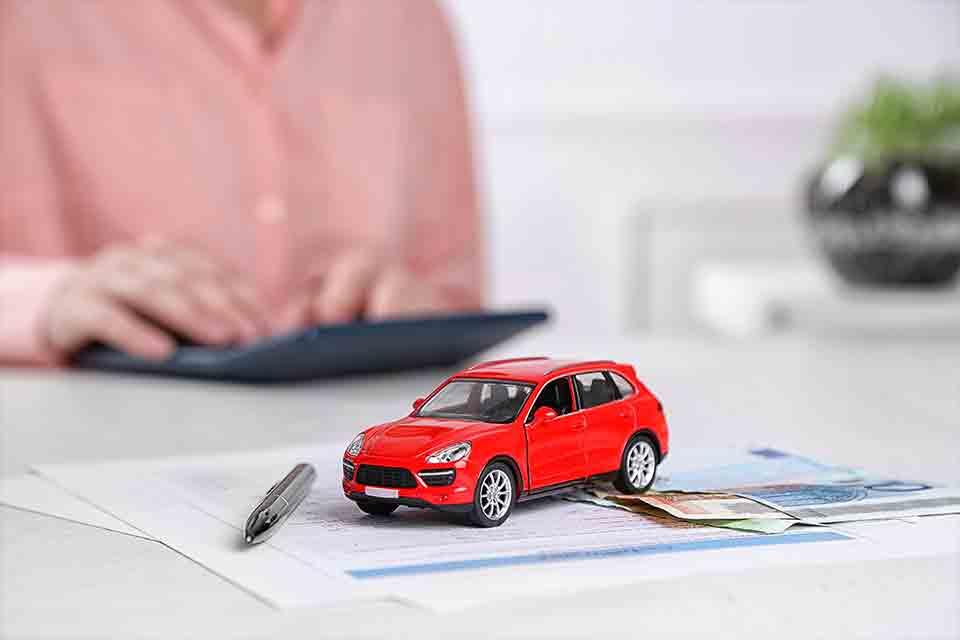 Sieviete rēķina uz kalkulatoru un uz galda stāv mašīna